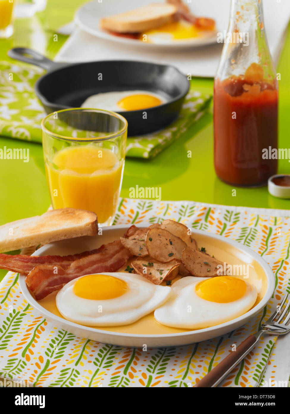 A breakfast scene with sunny side up fried eggs, bacon, toast, breakfast potatoes, and a glass of orange juice - Stock Image