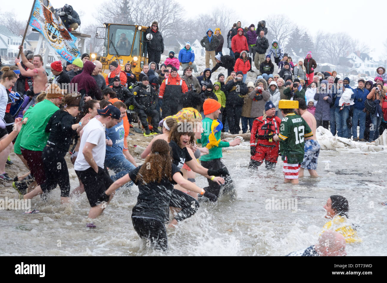 Fans watch swimmers splash around in ice water at Polar Plunge. - Stock Image