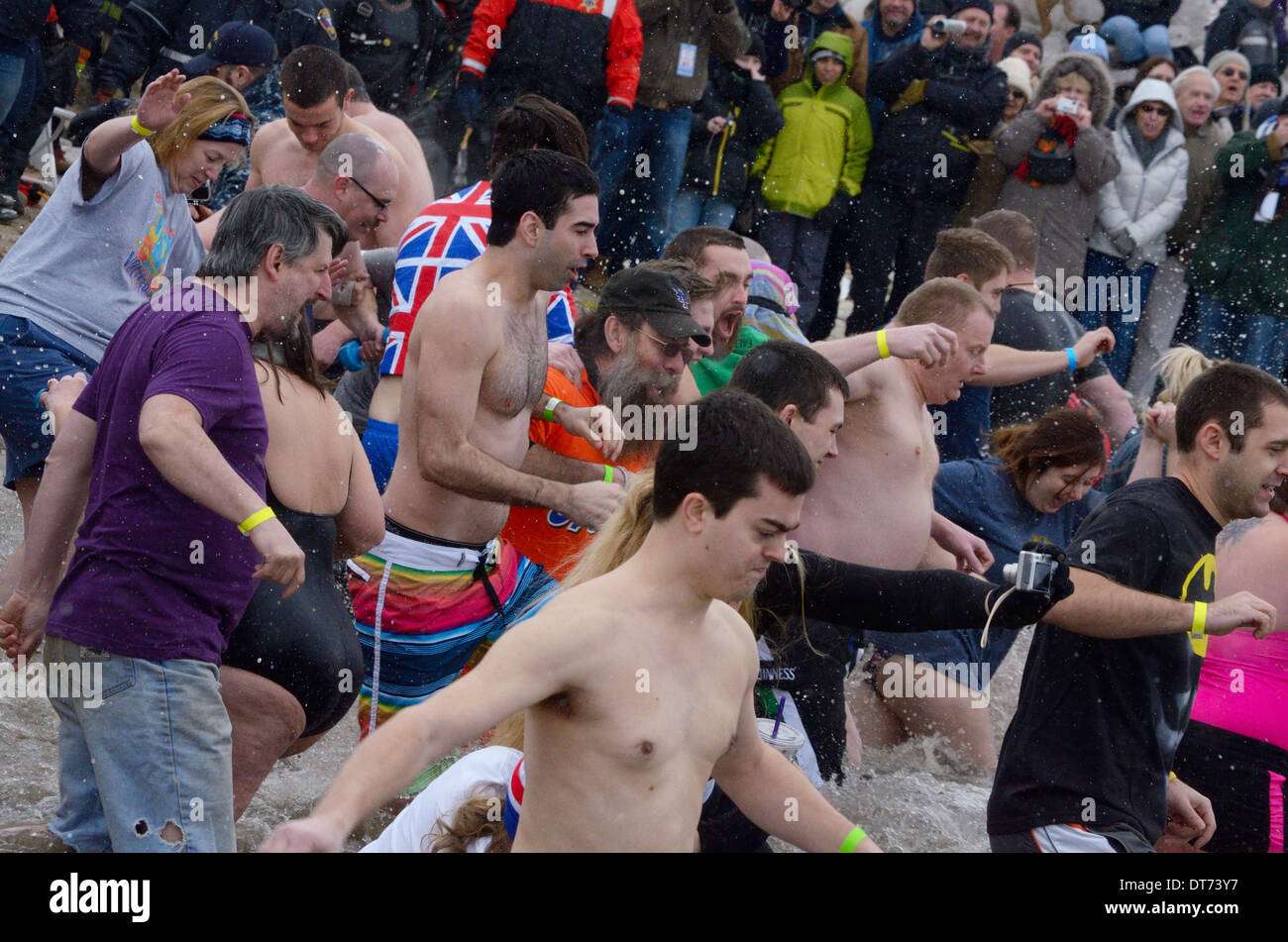 Waves of participants rush down beach to enter Polar Swim event - Stock Image