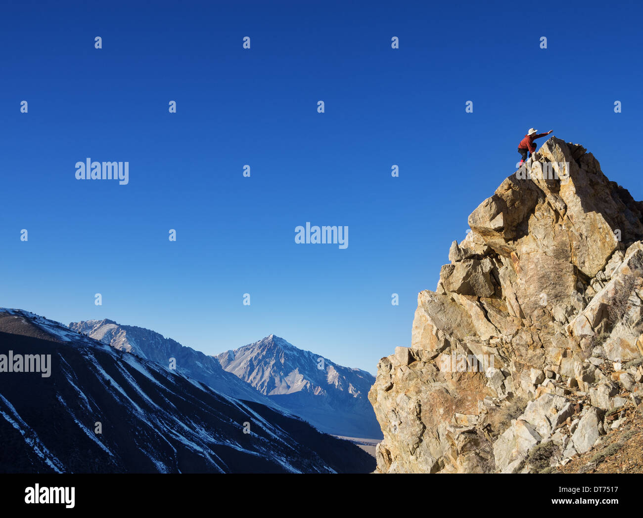 a man reaches his goal of a mountain top - Stock Image