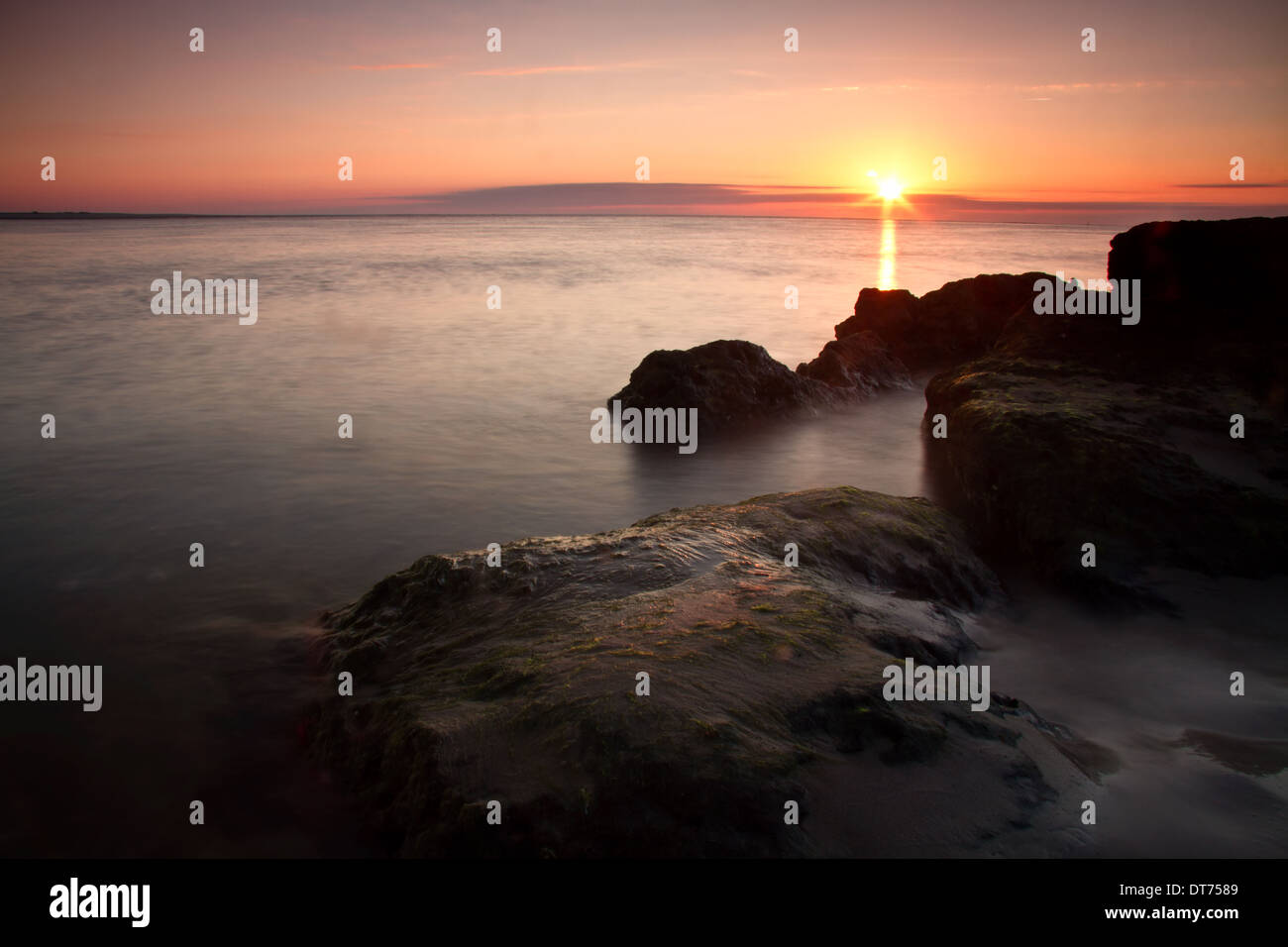Sunrise over the rocks on the beach. - Stock Image