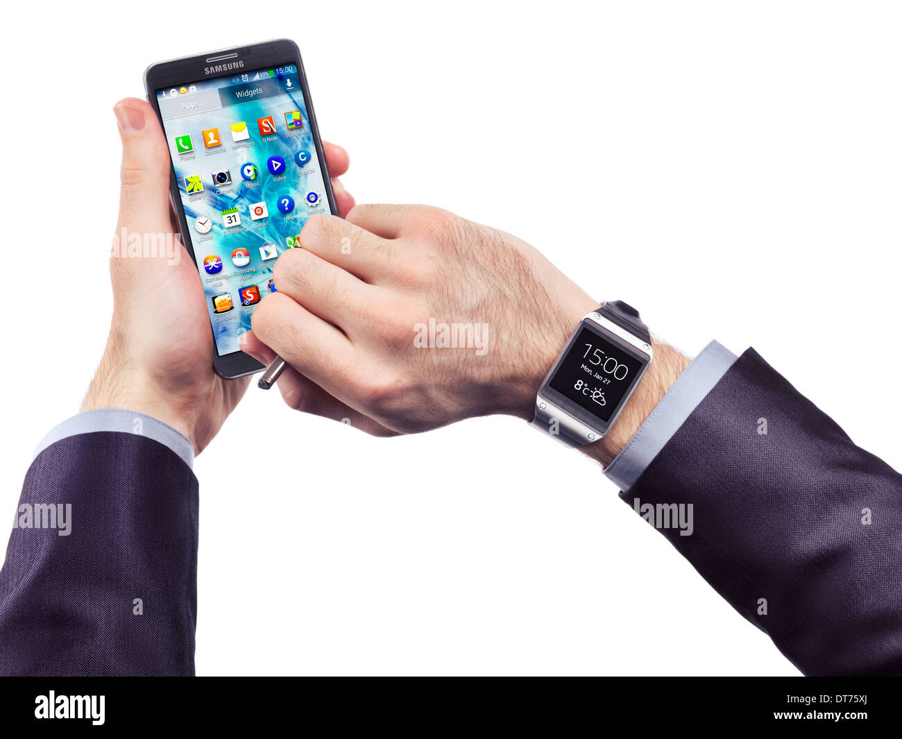 Hands of a person wearing Samsung Galaxy Gear watch and holding Galaxy Note 3 smartphone isolated on white background - Stock Image