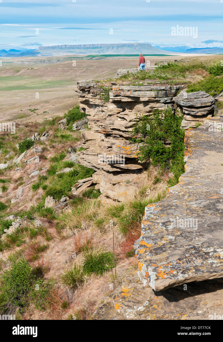 Montana, Ulm, First Peoples Buffalo Jump State Park, female visitor standing on precipice of jump cliff - Stock Image