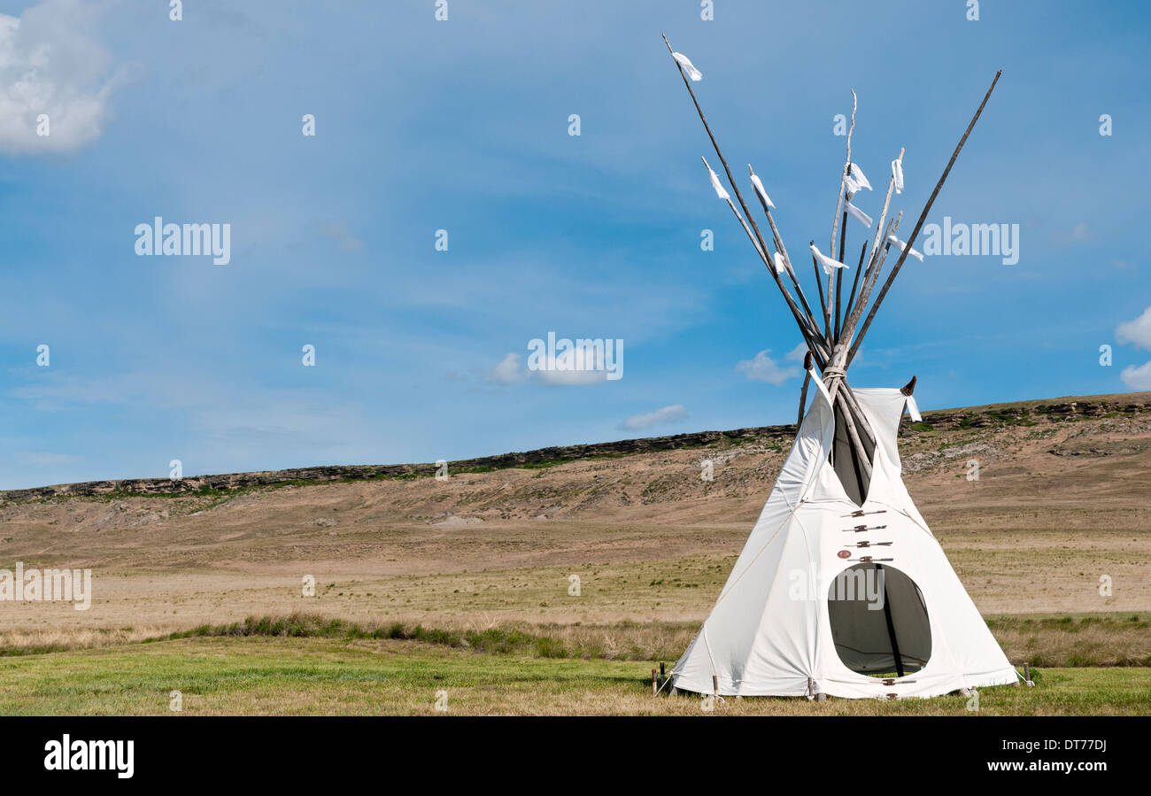 Montana, Ulm, First Peoples Buffalo Jump State Park, tepee (alt.sp. tipi, teepee) shelter, jump cliff in background - Stock Image