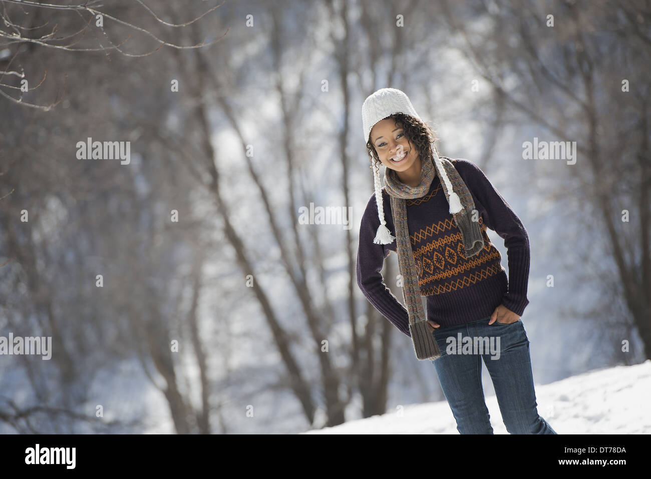 Winter scenery with snow on the ground. A young woman wearing a woolly hat. - Stock Image
