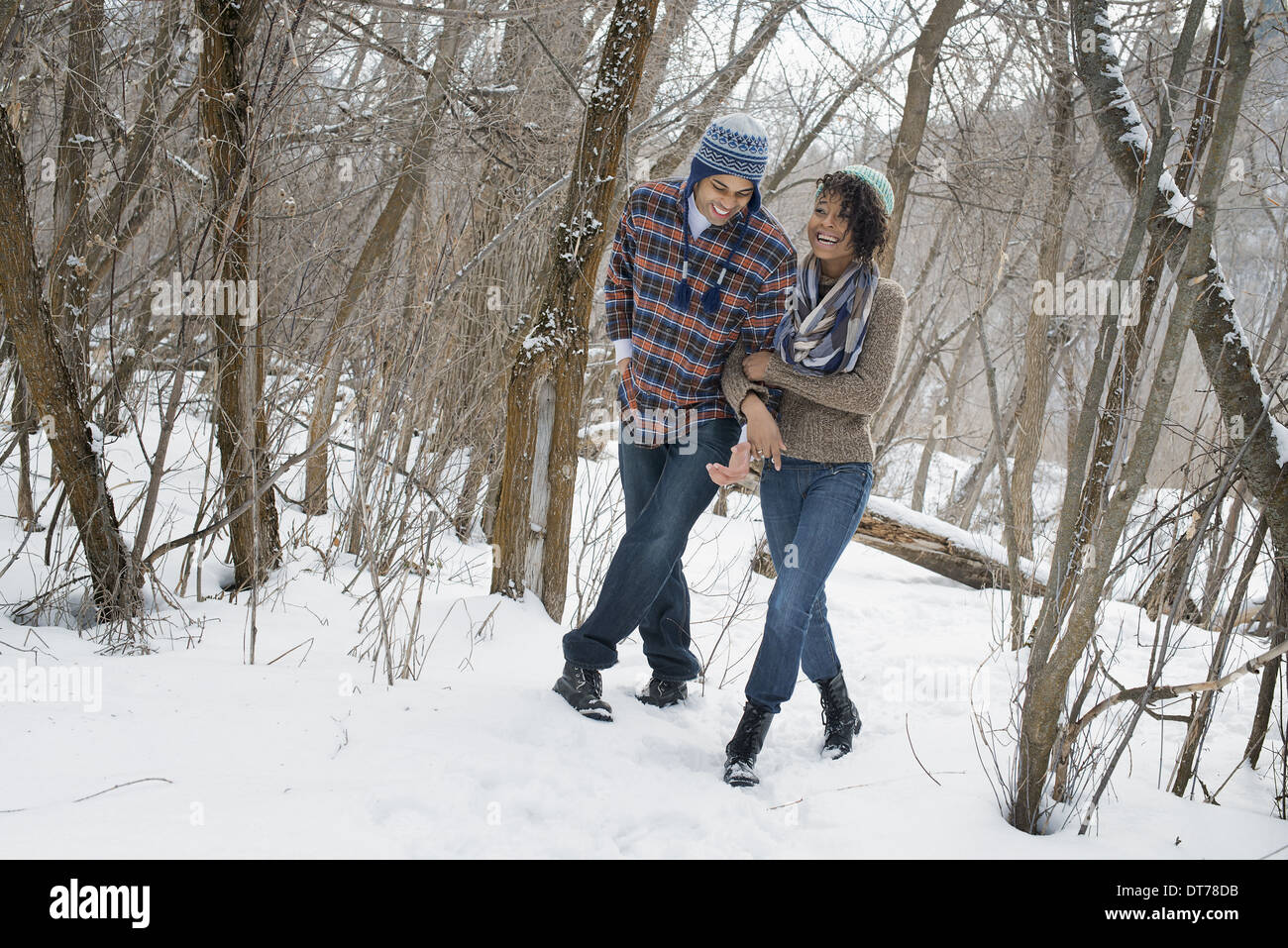 Winter scenery with snow on the ground. A couple arm in arm walking through the woods. - Stock Image