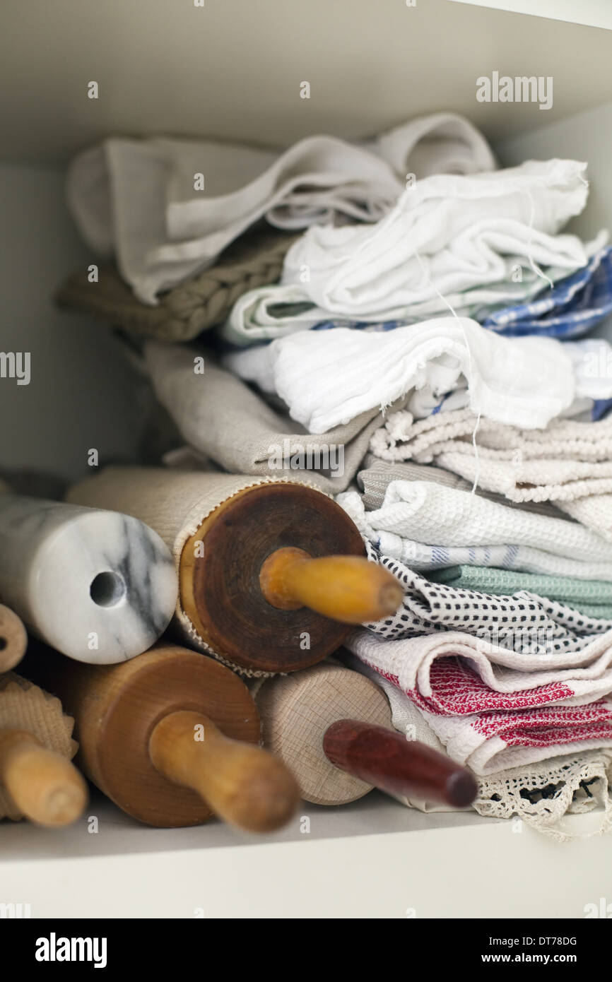 A shelf piled high with cloths, linen and a small stack of rolling pins or wooden spindles. - Stock Image