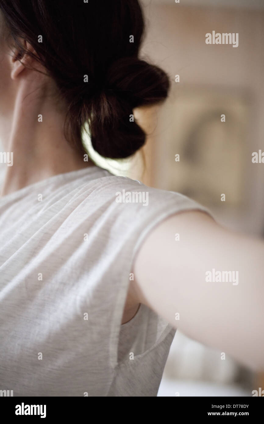 A woman wearing a light tee shirt, with her hair neatly tied back in a clip.  Stretching out her arms. - Stock Image