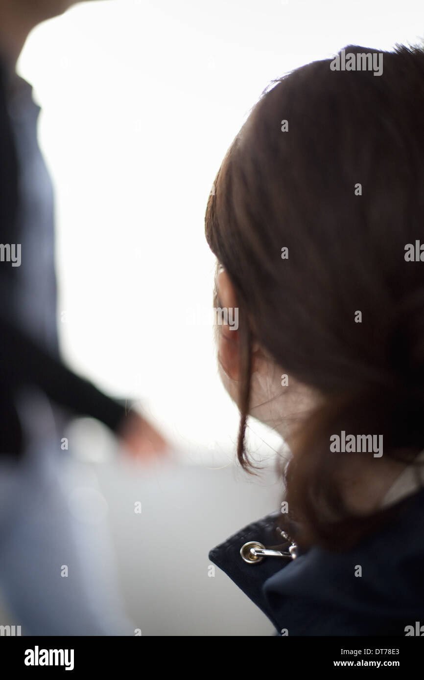 A woman with long brown hair tied back from her face. A blue jacket with the collar up. Side view. - Stock Image