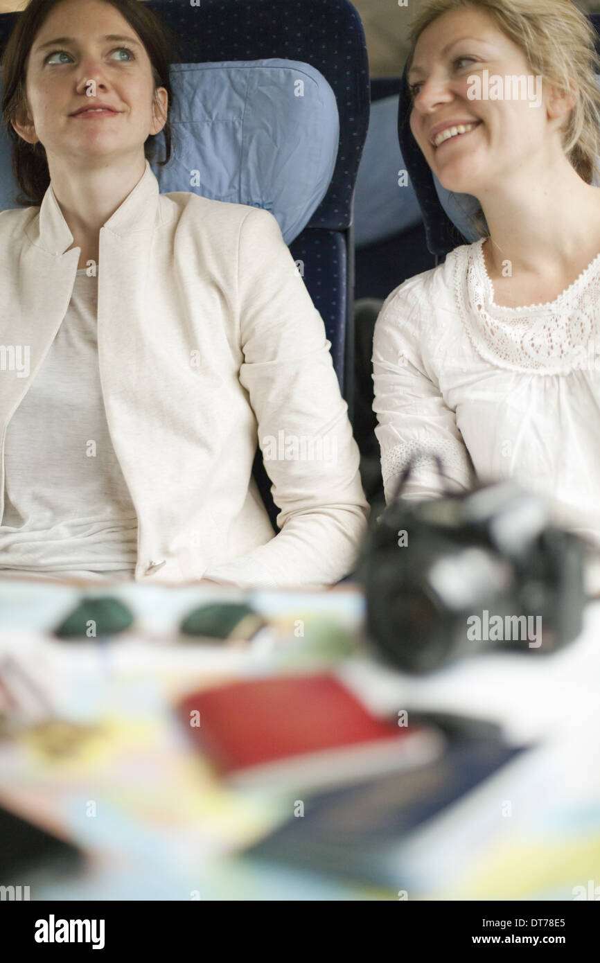 Two women seated on a train, side by side. Camera, passports and sunglasses on the table in front of them. - Stock Image
