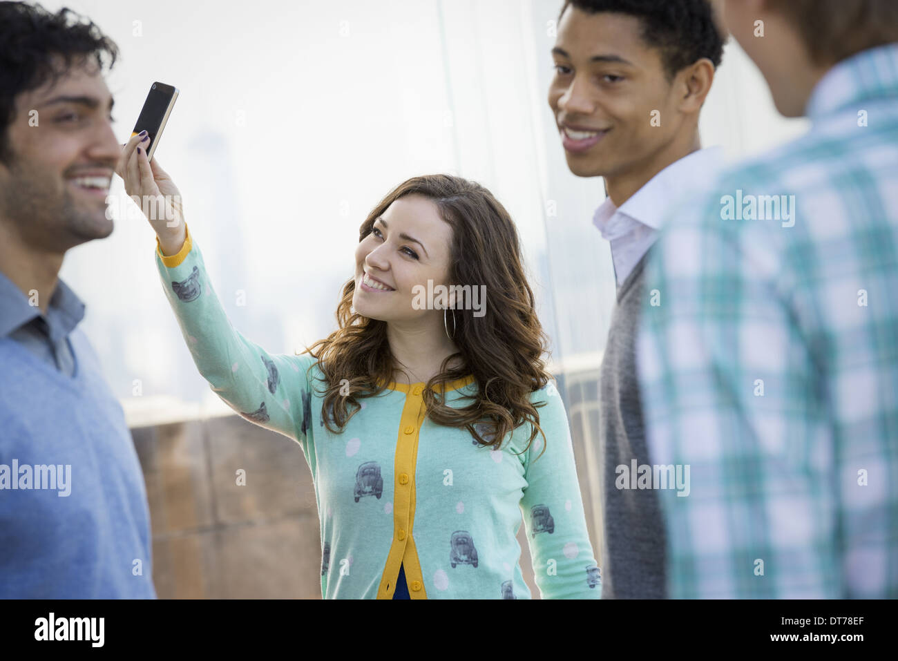 New York City. An observation deck Empire State Building. A woman using a smart phone to take an image. Three young men. - Stock Image