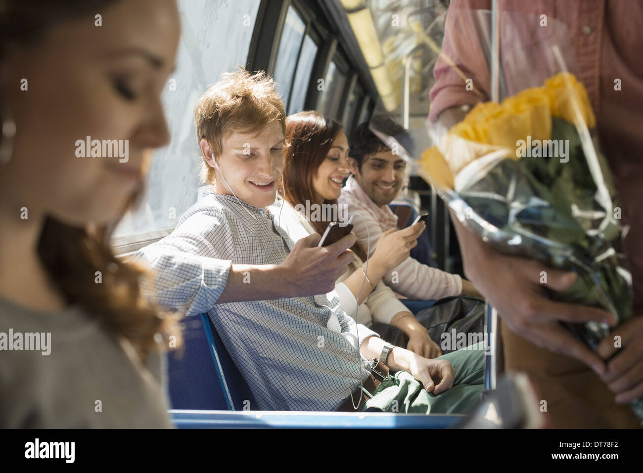 Urban Lifestyle. A group of people, men and women on a city bus, in New York city. Two people checking their smart phones. - Stock Image