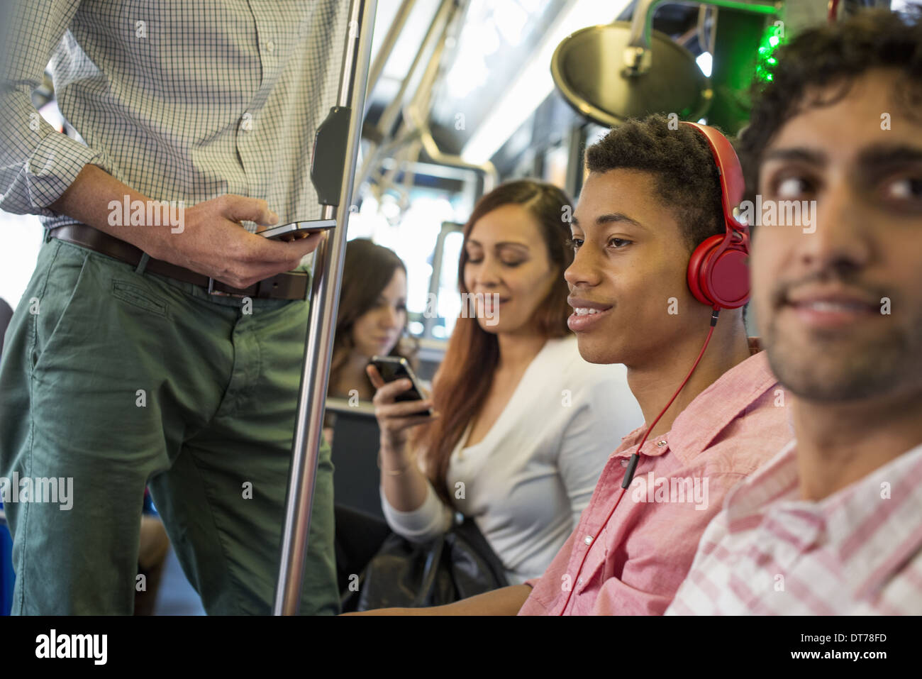 men and women on a city bus, in New York city. A man with headphones on. A man and a woman checking their smart phones. - Stock Image