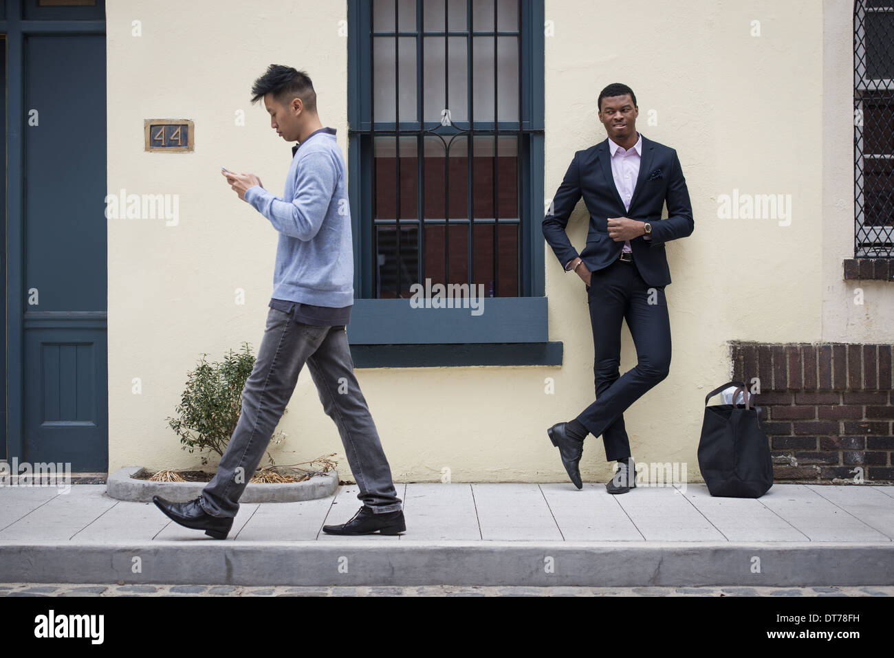 Young people outdoors on the city streets in springtime.  A man leaning against a wall and one walking past checking his phone. - Stock Image
