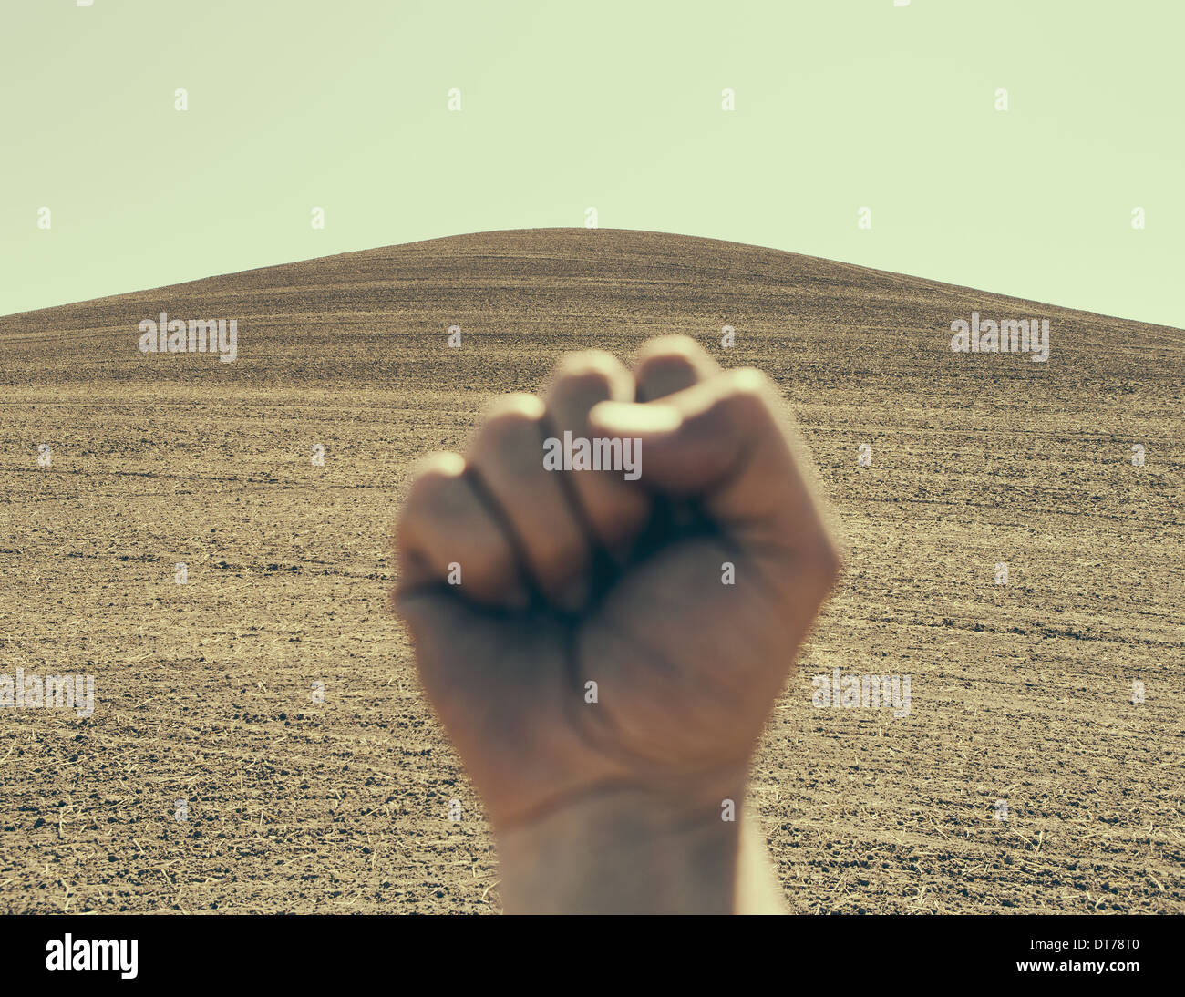 A hand bunched up and making a fist, against the background of a ploughed field and farmland. - Stock Image