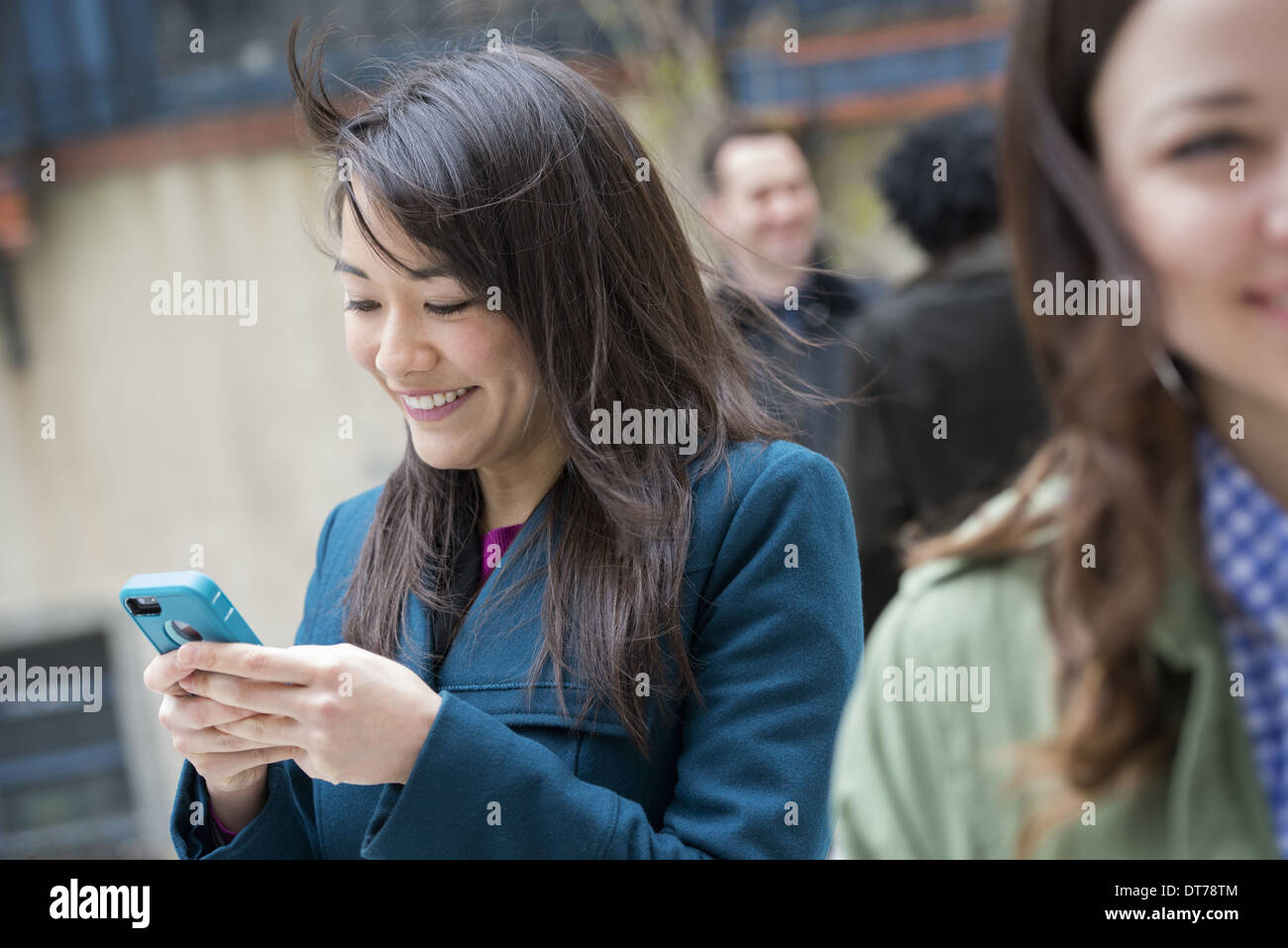 A woman checking her turquoise smart phone, among other people on a city street. - Stock Image