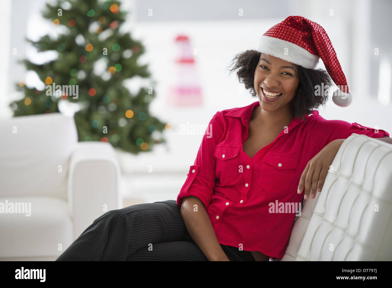 2376f39163 A woman wearing a red and white Father Christmas hat. Sitting on a sofa.
