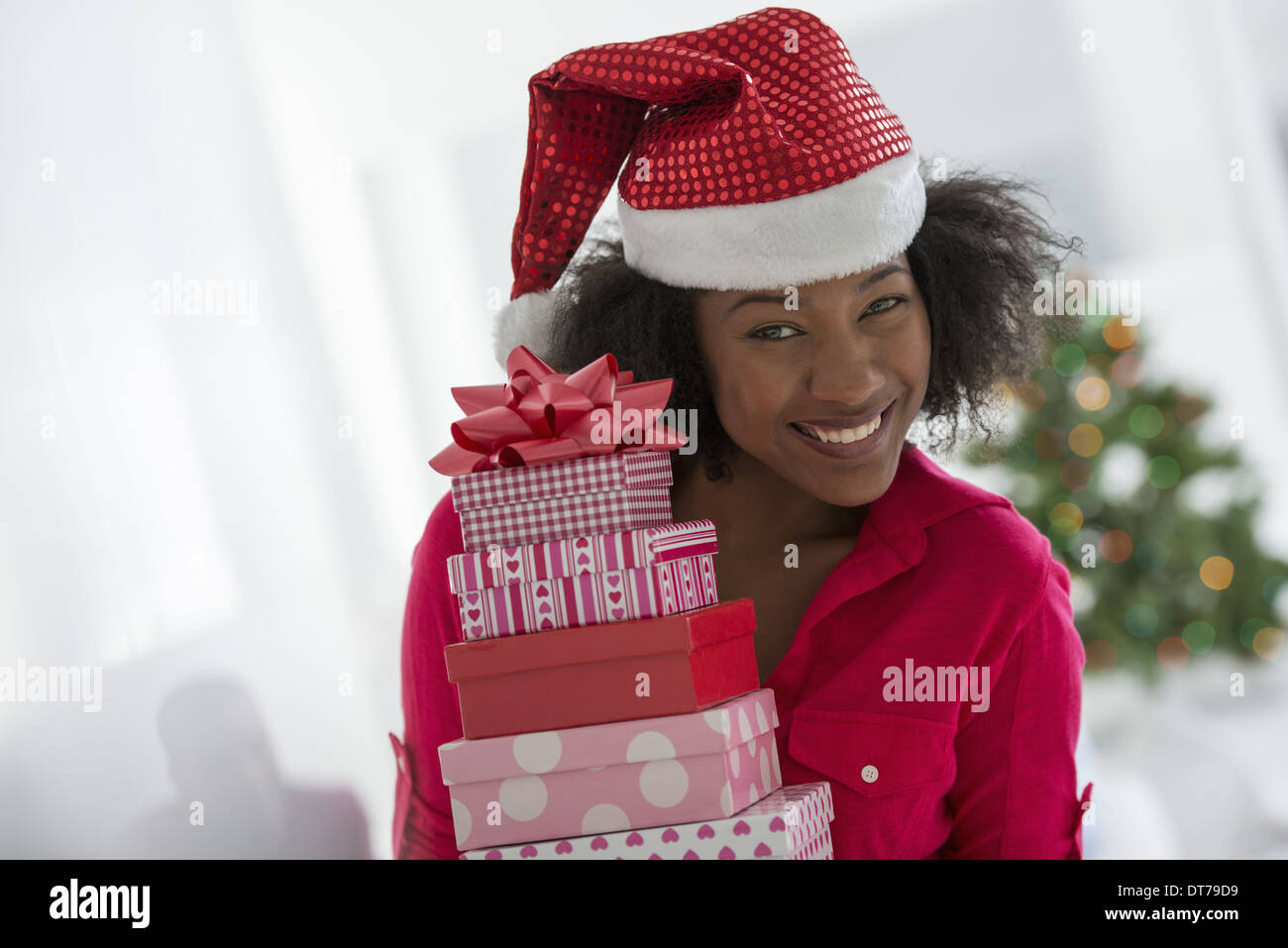 A woman wearing a red and white Father Christmas hat.  At home. A decorated Christmas tree. - Stock Image