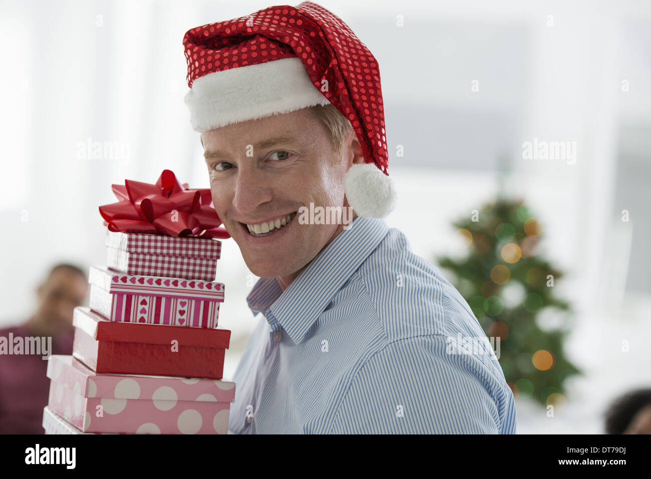 A man in a Father Christmas hat. At home. A decorated Christmas tree. - Stock Image