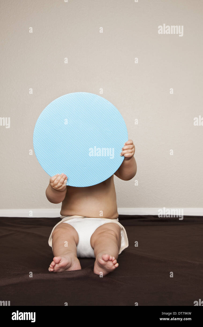 A young 8 month old baby boy wearing cloth diapers, hiding behind a large blue disc. - Stock Image