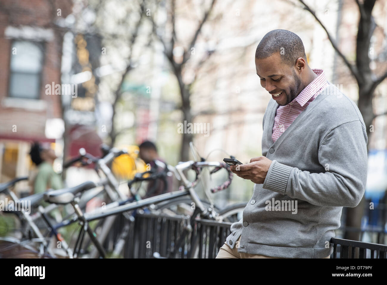 A man using his phone. A group of people in the background. Cycle rack. - Stock Image