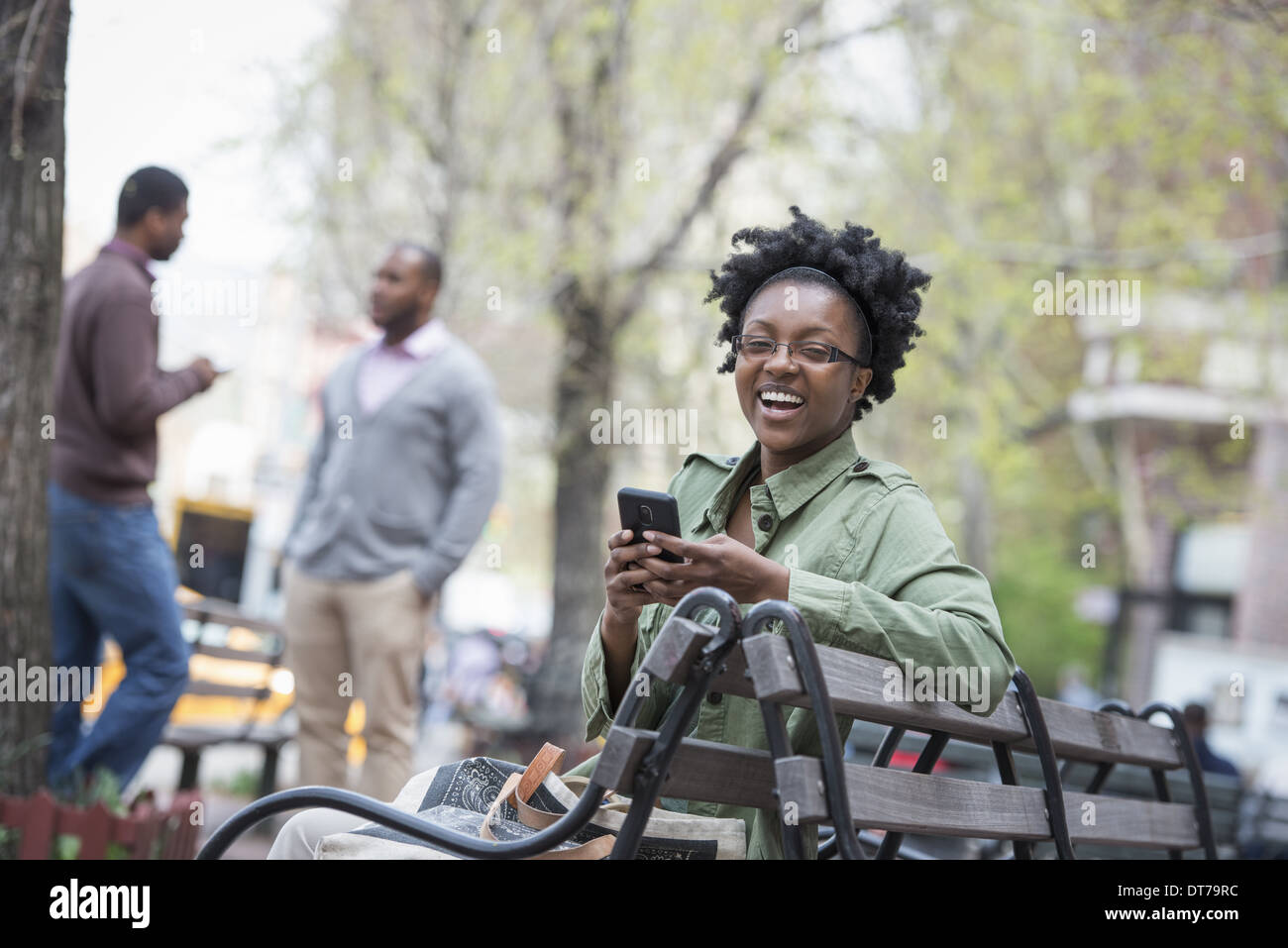 A woman on a bench checking her phone. Two men in the background. - Stock Image