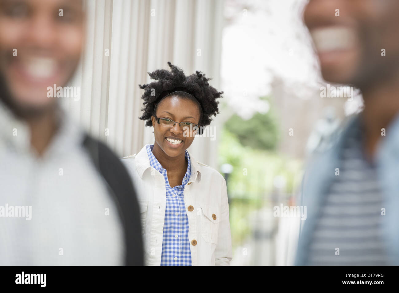 A woman looking at the camera, with two men in the foreground. - Stock Image