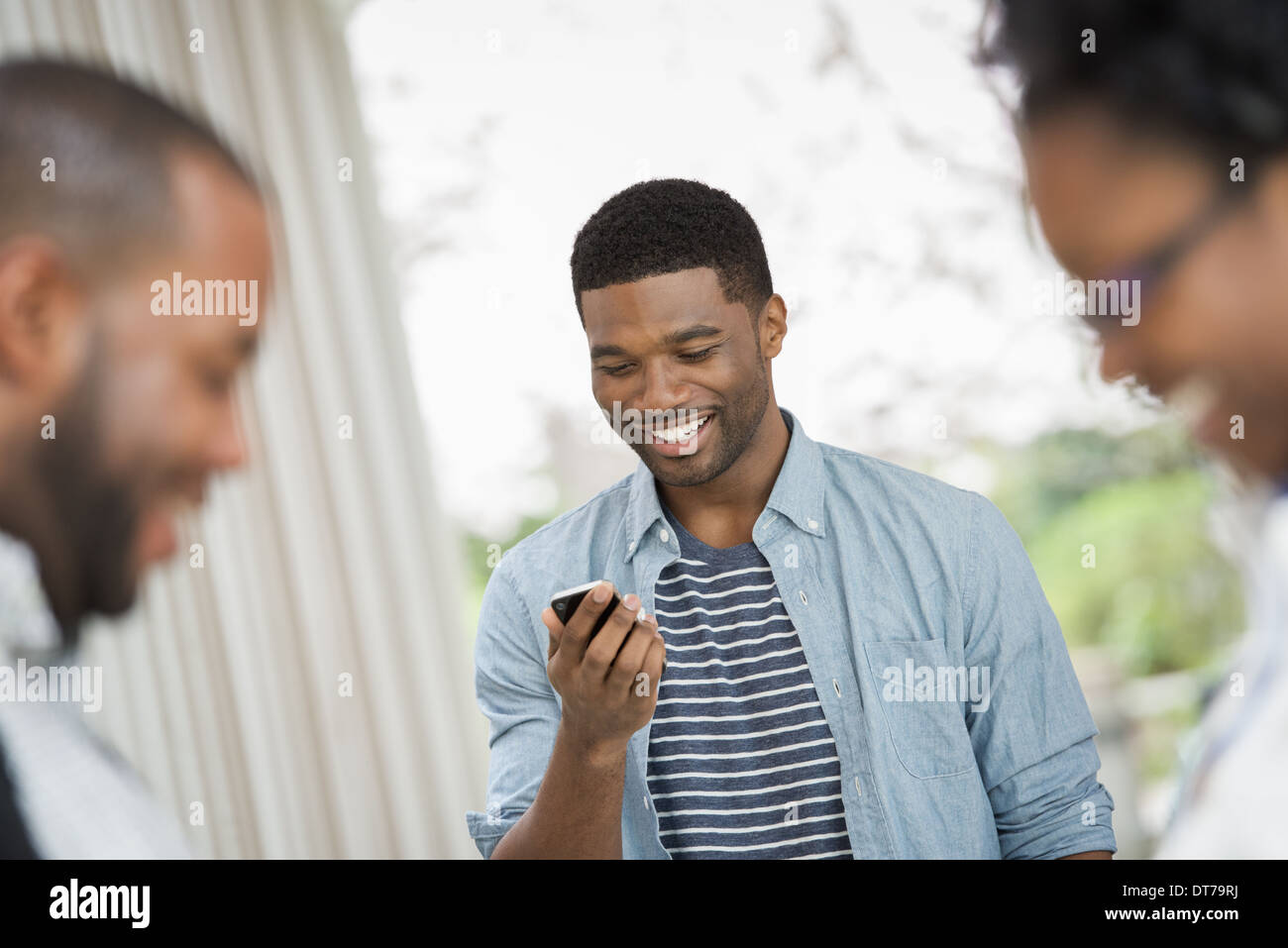 A young man checking his phone, behind a couple in the foreground. - Stock Image
