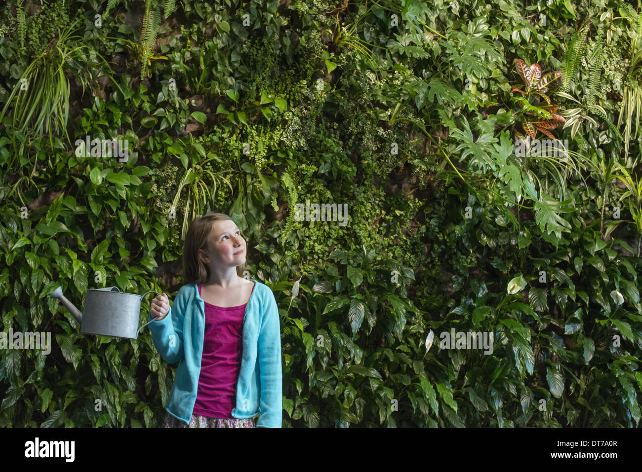 A young girl standing in front of a wall covered with ferns and climbing plants. - Stock Image