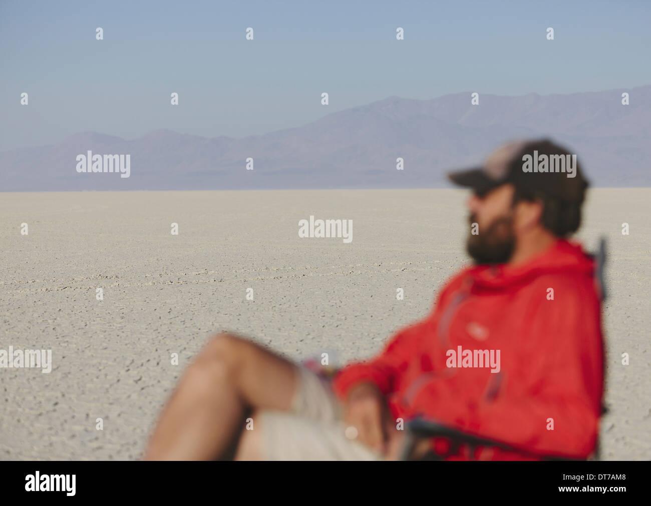 Man sitting in chair in vast barren desert blurred focus Black Rock Desert Pershing County Nevada USA USA - Stock Image