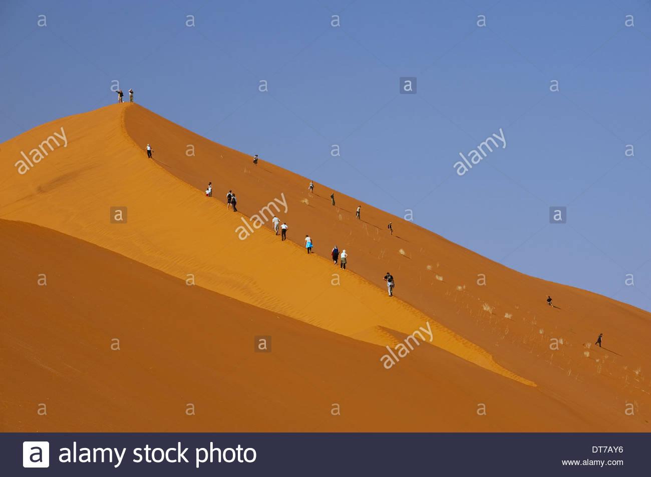 Hikers climbing up a sand dune ridge at Sossusvlei Namib-Naukluft National Park Namibia natural world landscape - Stock Image