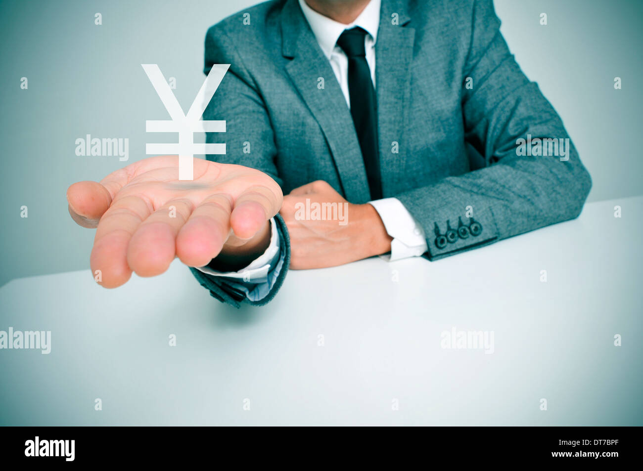 a businessman sitting in a desk showing a chinese yuan or japanese yen sign in his hand - Stock Image