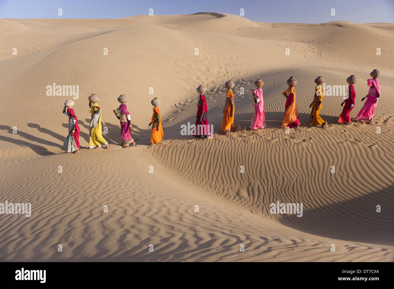 Rajasthan India Thar Desert Trekking up the side of a sand dunewomen carrying large water pots balanced on their heads - Stock Image