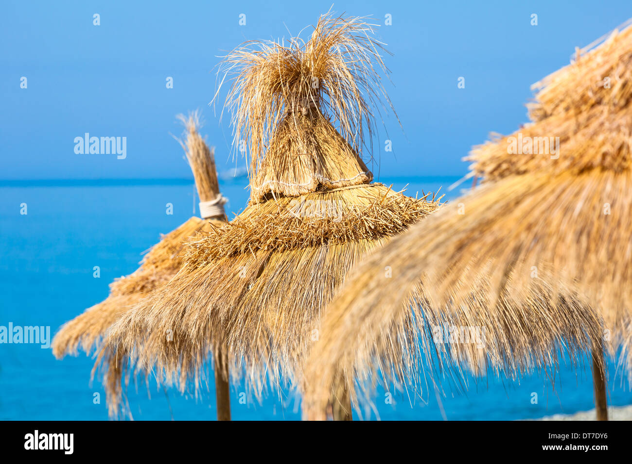 Yellow straw umbrella hats against blue sky-water background. Focus on the central hat - Stock Image