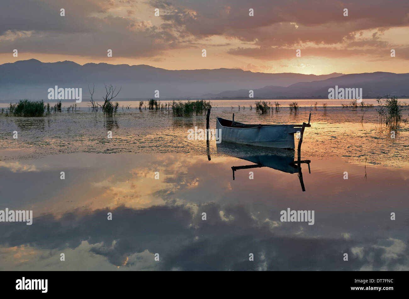 Fishing boat in lake at rising sun - Stock Image