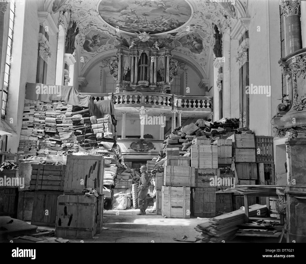 A US soldier from the Third Army views stacks of jewish owned art looted by the Nazi hidden in a church April 24, 1945 in Ellingen, Germany. - Stock Image