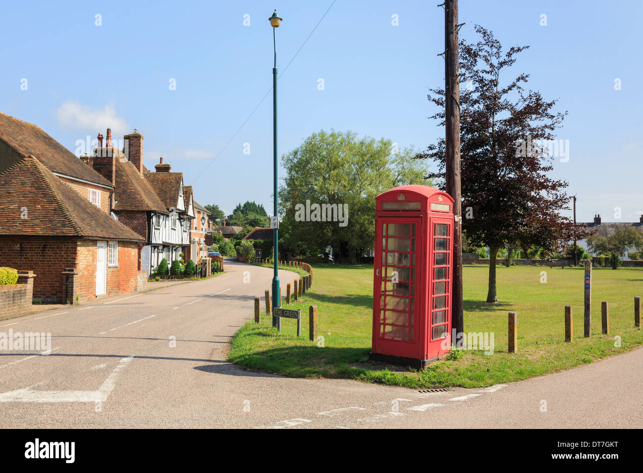 Traditional old red telephone box and telegraph pole on a village green in Stour Valley. Chartham, Kent, England, UK, Britain - Stock Image