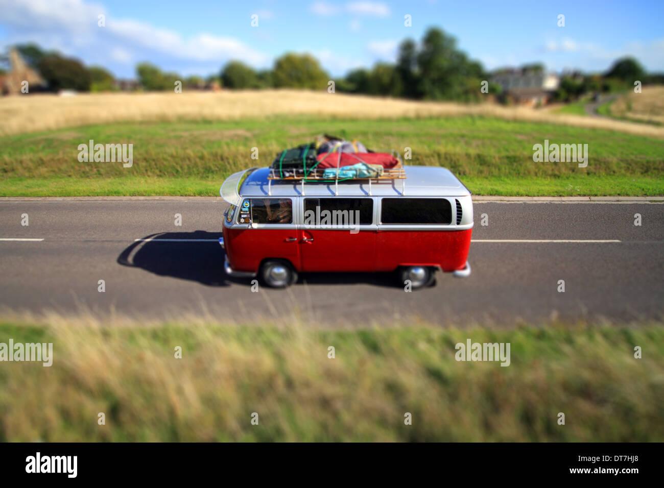 Volkswagen campervan driving along road - Stock Image