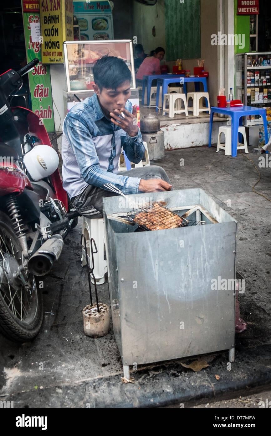 HANOI, VIETNAM, JANUARY 27: Vietnamese man cooking on the street. A common sight in the countries capital city Hanoi. Stock Photo