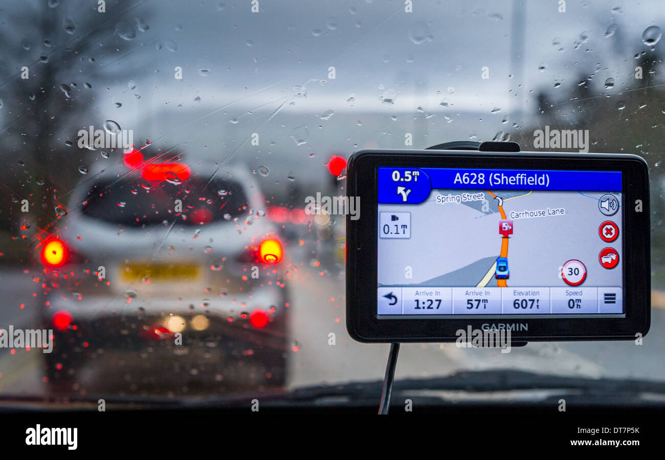 Satnav monitor attached to a car window on a wet day. - Stock Image