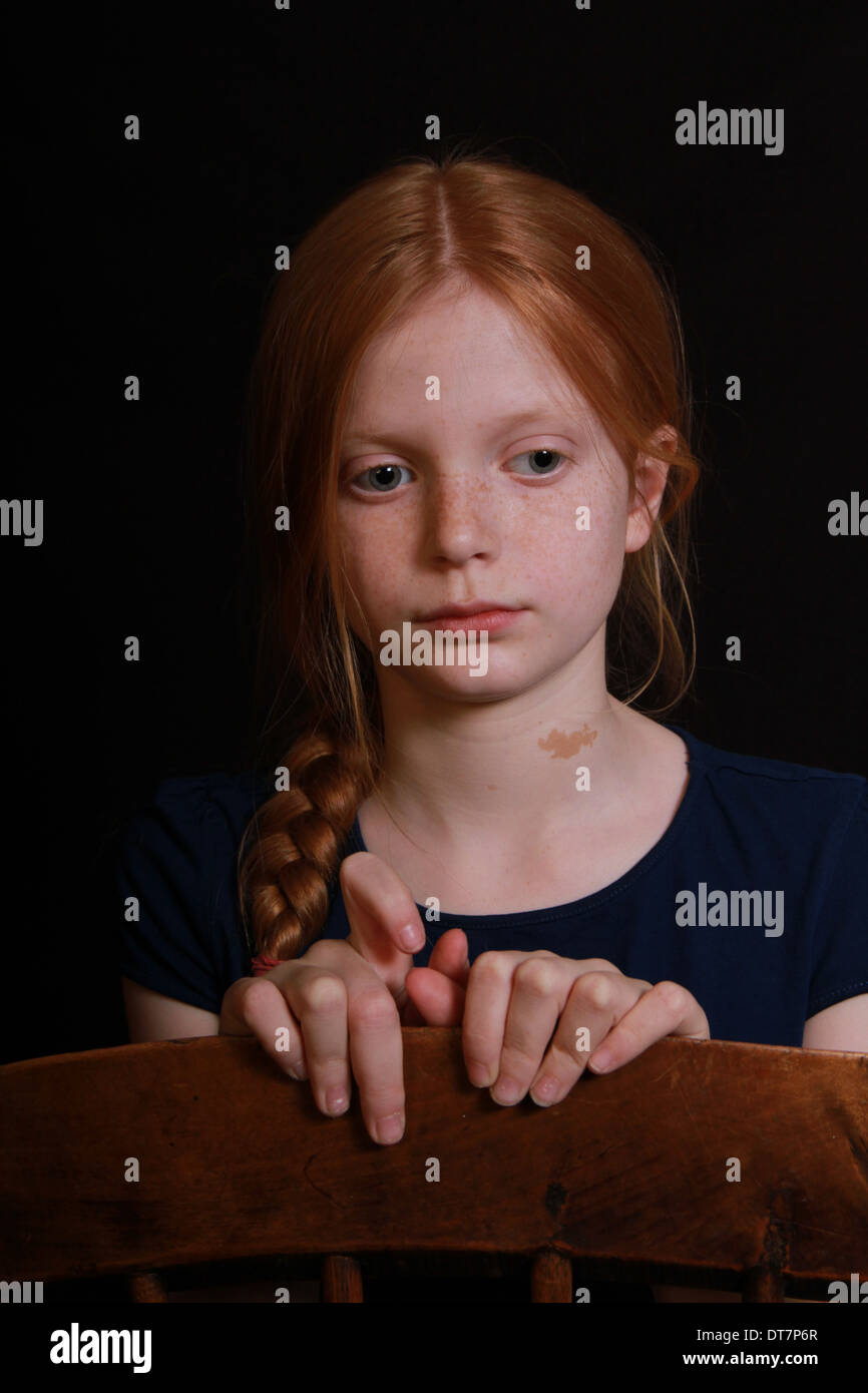 A beautiful red-headed child with her hair in a plait stares away from the camera. She looks pensive the background is dark. - Stock Image