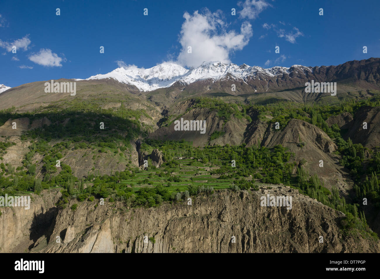 Village and terraces built into the side of a steep valley, with the snow-capped Rakaposhi range behind, seen from the Karakoram Highway between the Hunza Valley and Gilgit, Gilgit-Baltistan, Pakistan - Stock Image