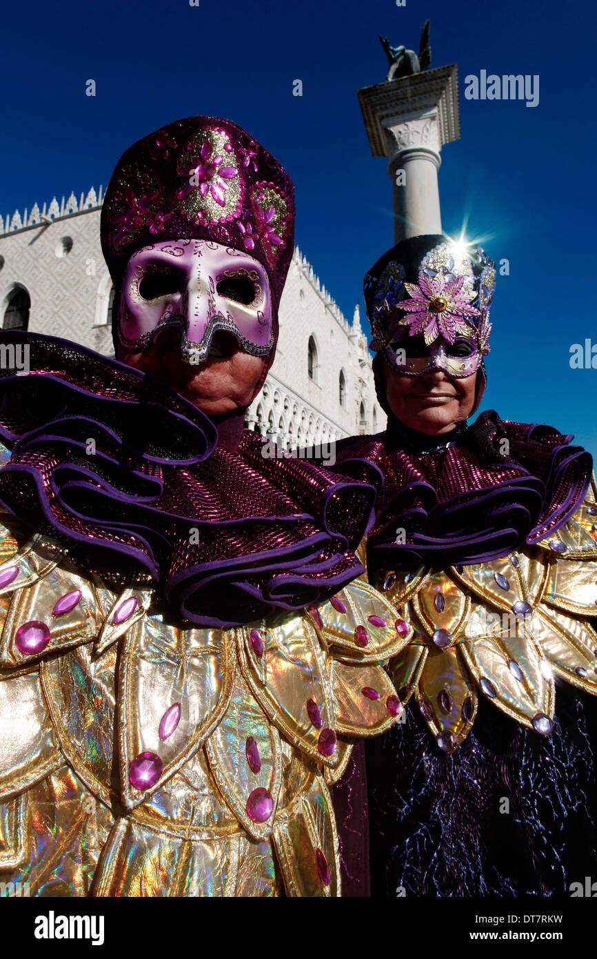 Two masked people posing at Carnival of Venice with Ducale Building on the background Stock Photo