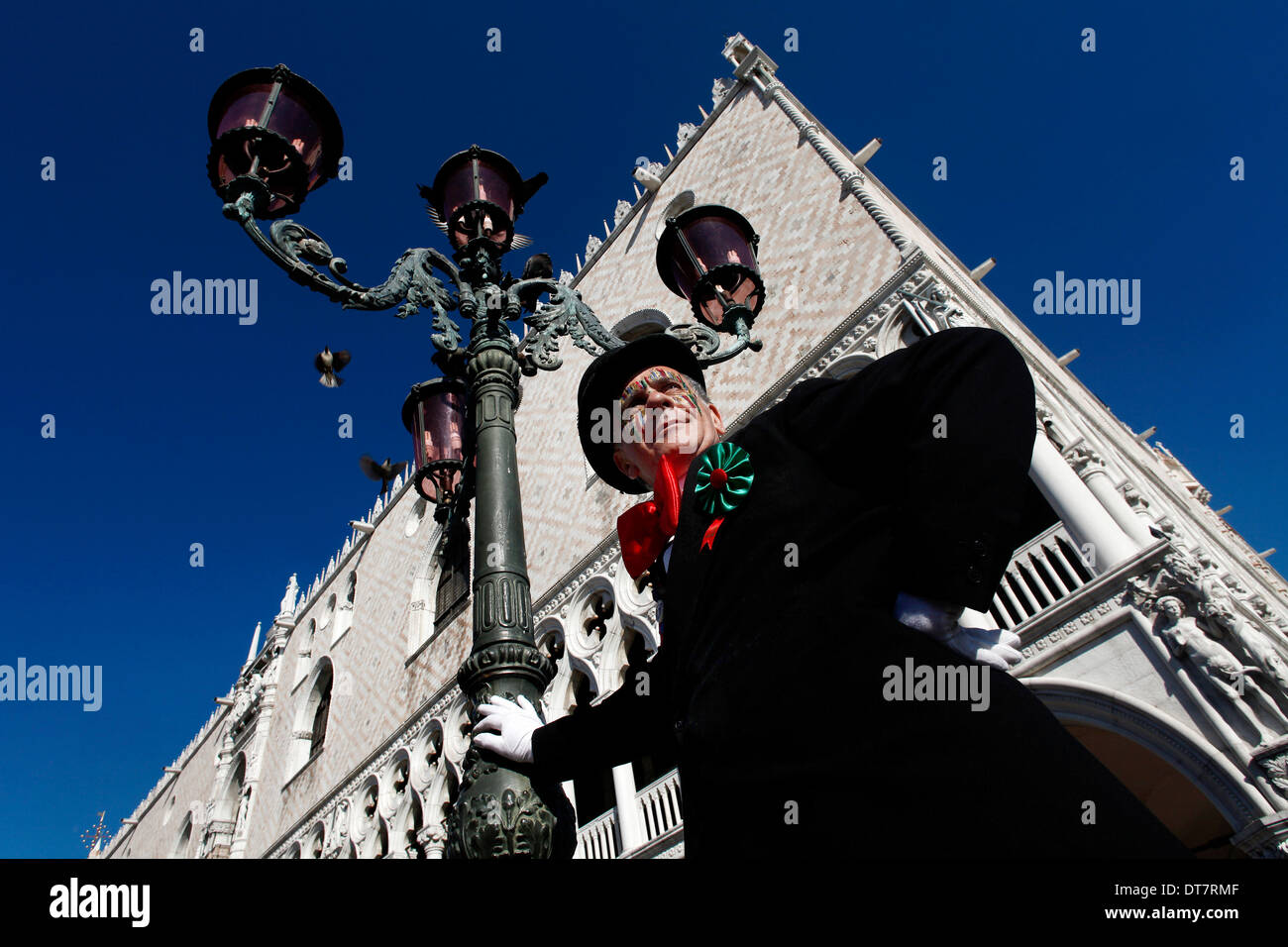 A masked man at Carnival of Venice rested on a lamp-post with Ducale building on the background - Stock Image