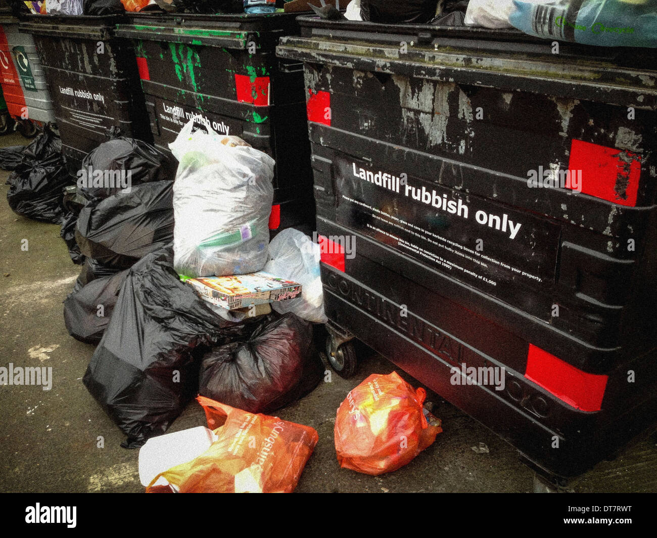 Large wheeled bins for Landfill with overflowing plastic bags - Stock Image