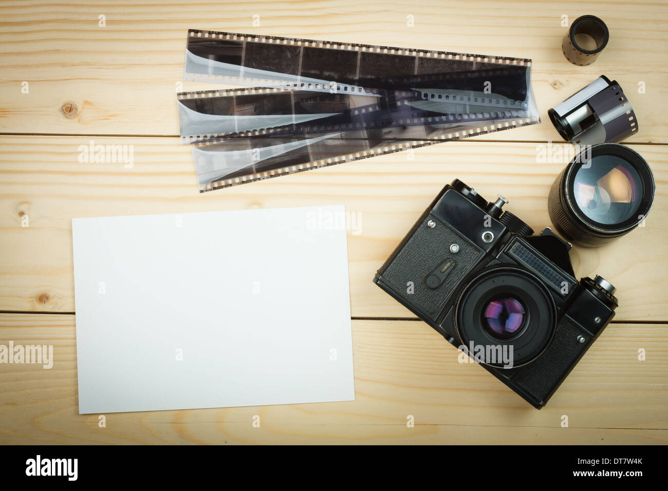 Old retro camera and film roll on wooden boards. Stock Photo