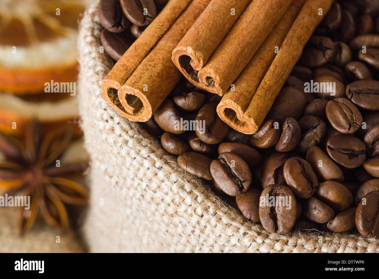 Aromatic coffee beans and cinnamon in burlap bag - Stock Image
