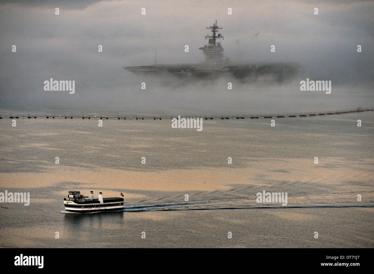 San Diego, CA, USA . 11th Feb, 2014. A commuter ferry passes the US Navy nuclear aircraft carrier USS Ronald Reagan enveloped in fog as she sits at her berth February 11, 2014 in San Diego, CA. Credit:  Planetpix/Alamy Live News - Stock Image