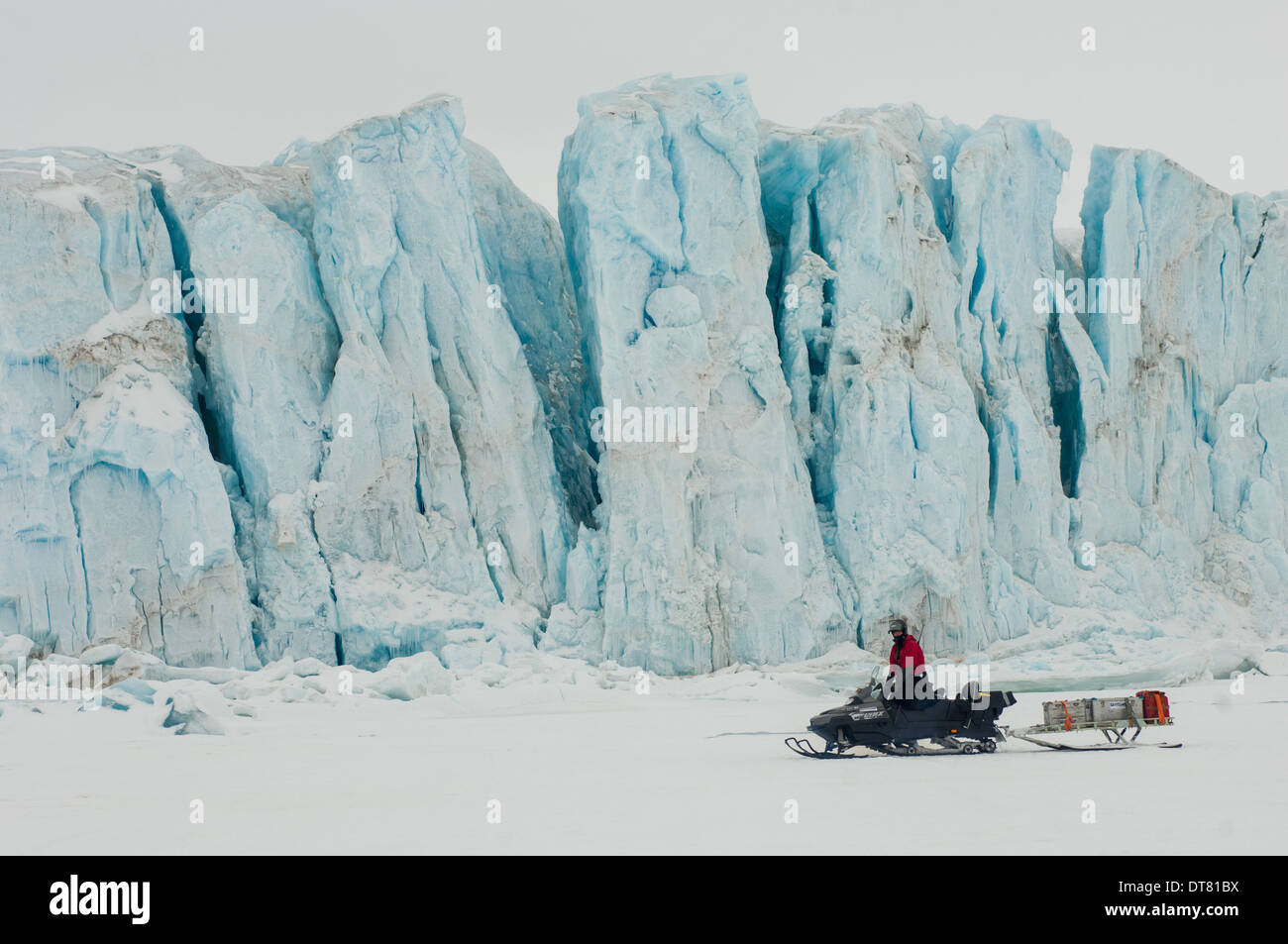 Arctic guide on a snowmobile in front of the Tuna Glacier (Tunabreen), Temple Fjord (Tempelfjorden), Spitsbergen, Svalbard Archipelago, Norway - Stock Image