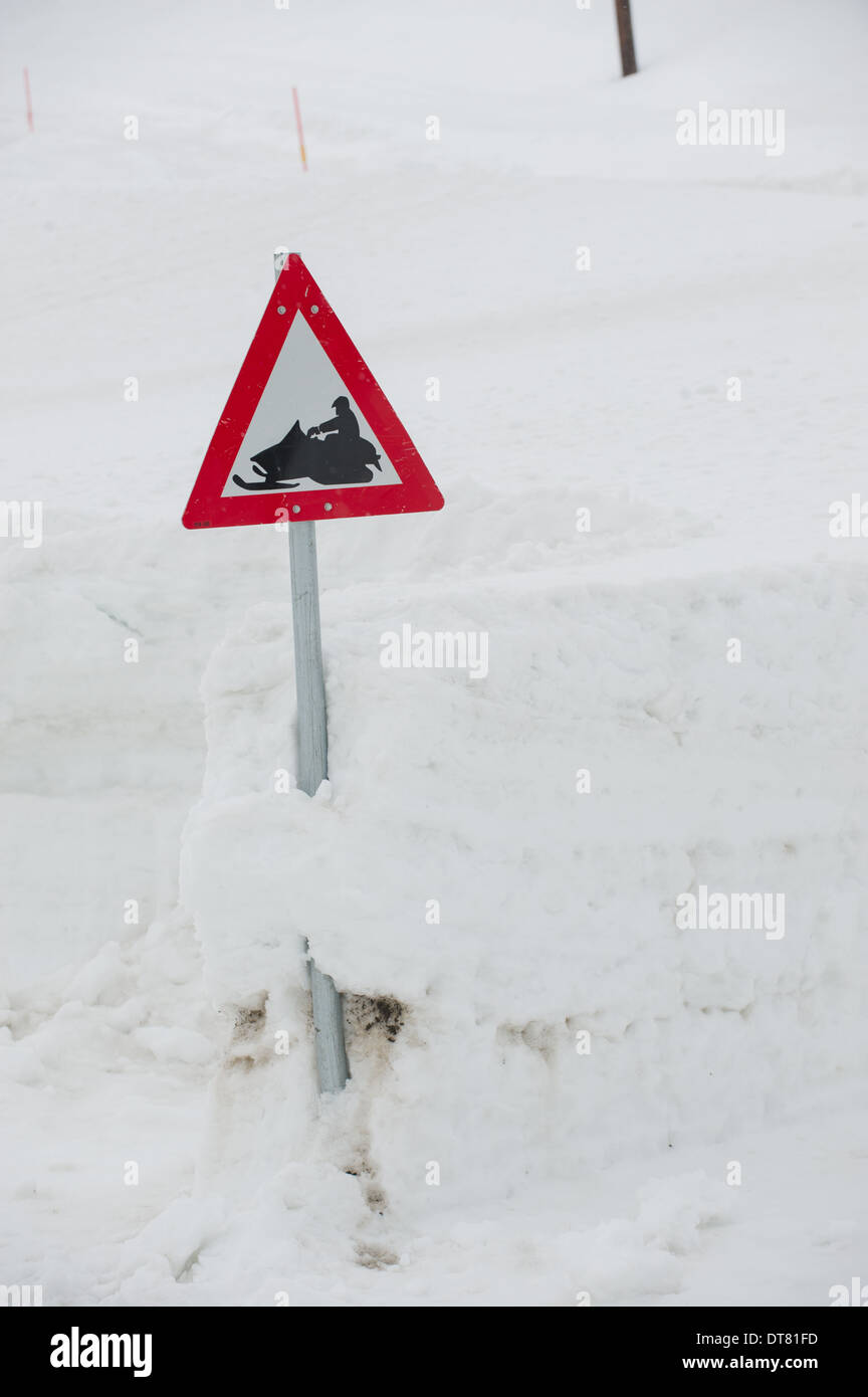 Snowmobile warning sign in a deep snow drift, Longyearbyen, Spitsbergen, Svalbard Archipelago, Norway - Stock Image